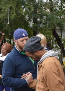 Church Planter Josh Holland prays with a man on the streets of New Orleans as Level Ground Community Church, 2 years old participates in a gift distribution.